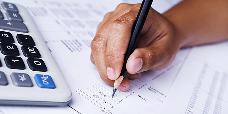 person writing beside calculator