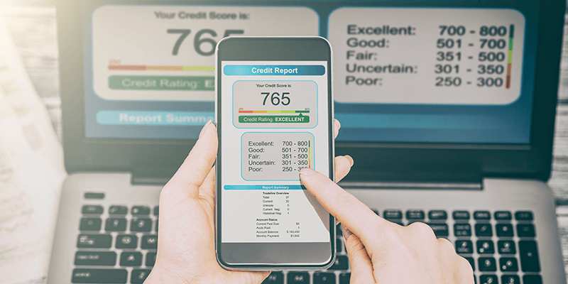 A laptop and phone showing credit report data.